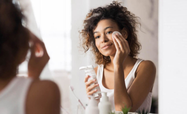 Young woman cleansing her face in bathroom mirror